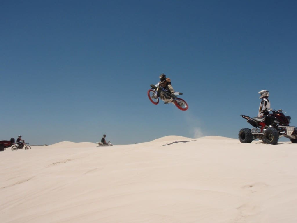 A motorbike jumping a dune