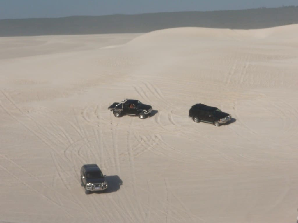 Several 4wd's waiting to drive up a dune