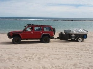 Driving on the beach with a camper trailer
